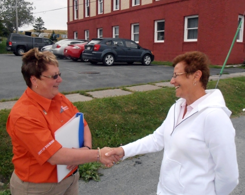 Lois Dawe, Tourism Officer, greets tour member in front of Cable Building.